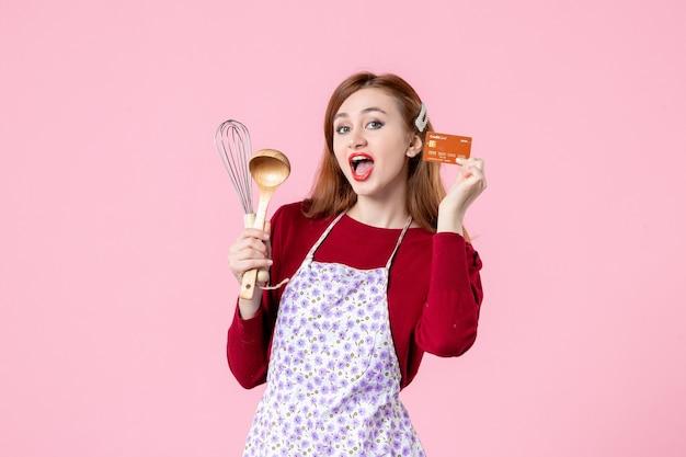 Widok z przodu młoda gospodyni trzymająca trzepaczkę i kartę bankową na różowym tle kolor ciasto kuchnia zakupy gotowanie kuchnia kobieta jedzenie pieniądze