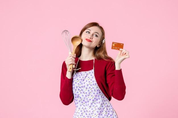 Widok z przodu młoda gospodyni trzymająca trzepaczkę i kartę bankową na różowym tle kolor ciasto kuchnia zakupy kuchnia kobieta ciasto jedzenie pieniądze