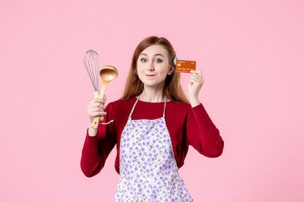 Widok z przodu młoda gospodyni trzymająca trzepaczkę i kartę bankową na różowym tle kolor ciasto słodka kuchnia gotowanie kuchnia ciasto jedzenie