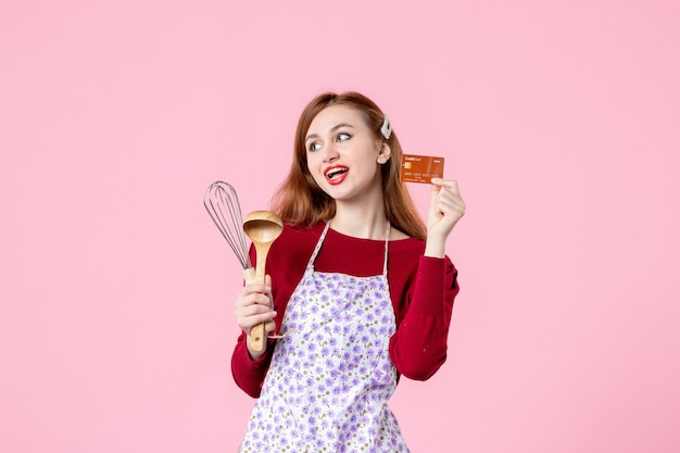 Widok z przodu młoda gospodyni trzymająca trzepaczkę i kartę bankową na różowym tle kolor ciasto słodka kuchnia gotowanie kuchnia kobieta ciasto jedzenie