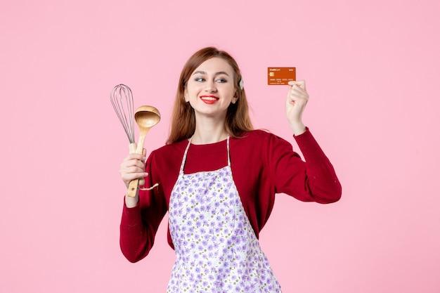 Widok z przodu młoda gospodyni trzymająca trzepaczkę i kartę bankową na różowym tle kolor ciasto słodka kuchnia gotowanie kuchnia kobieta jedzenie