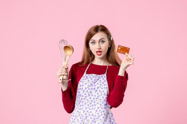 Widok z przodu młoda gospodyni trzymająca trzepaczkę i kartę bankową na różowym tle kolor ciasto zakupy gotowanie kuchnia kobieta ciasto jedzenie pieniądze