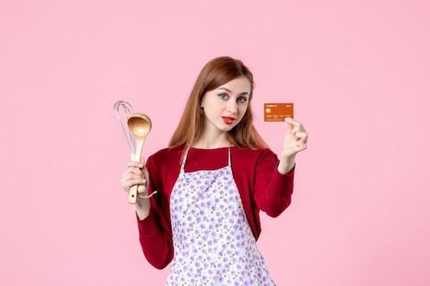 Widok z przodu młoda gospodyni trzymająca trzepaczkę i kartę bankową na różowym tle kolory ciasto kuchnia zakupy gotowanie kuchnia kobieta ciasto jedzenie pieniądze
