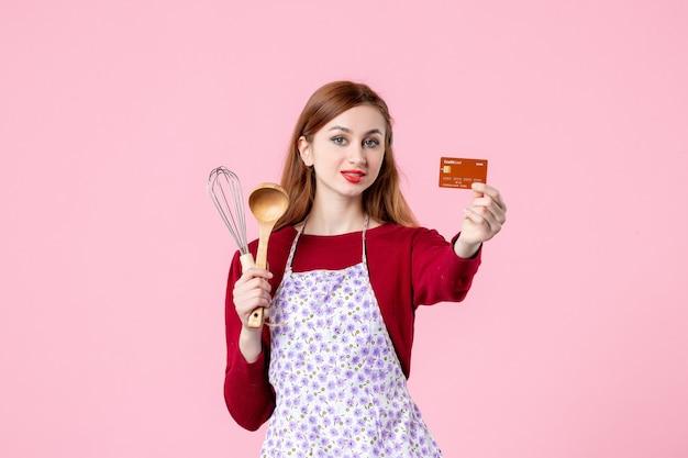 Widok z przodu młoda gospodyni trzymająca trzepaczkę i kartę bankową na różowym tle kuchnia ciasto ciasto kobieta kolor gotowanie pieniądze kuchnia jedzenie