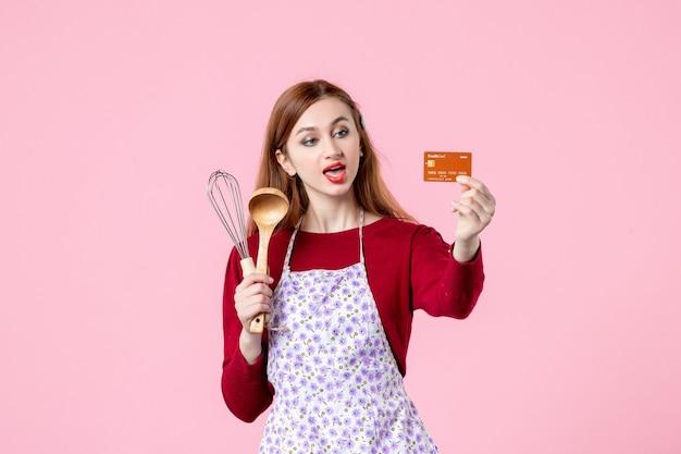 Widok z przodu młoda gospodyni trzymająca trzepaczkę i kartę bankową na różowym tle kuchnia ciasto ciasto kobieta kolor zakupy gotowanie kuchnia jedzenie
