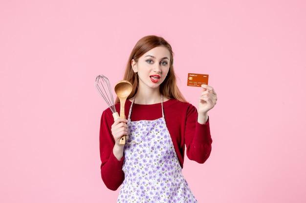 Widok z przodu młoda gospodyni trzymająca trzepaczkę i kartę bankową na różowym tle kuchnia ciasto ciasto kobieta kolor zakupy gotowanie pieniądze kuchnia jedzenie