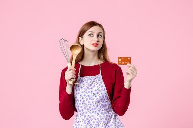 Widok z przodu młoda gospodyni trzymająca trzepaczkę i kartę bankową na różowym tle kuchnia ciasto ciasto kobieta kolor zakupy gotowanie pieniądze kuchnia