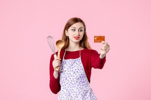 Widok z przodu młoda gospodyni trzymająca trzepaczkę i kartę bankową na różowym tle kuchnia ciasto ciasto kobieta kolor zakupy pieniądze kuchnia jedzenie