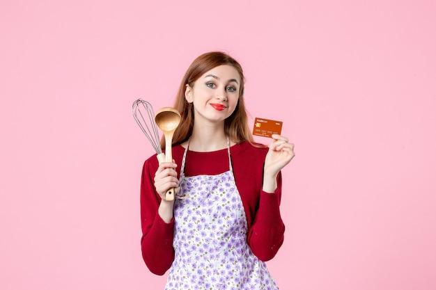 Widok z przodu młoda gospodyni trzymająca trzepaczkę i kartę bankową na różowym tle kuchnia ciasto ciasto kobieta zakupy gotowanie pieniądze kuchnia jedzenie kolory