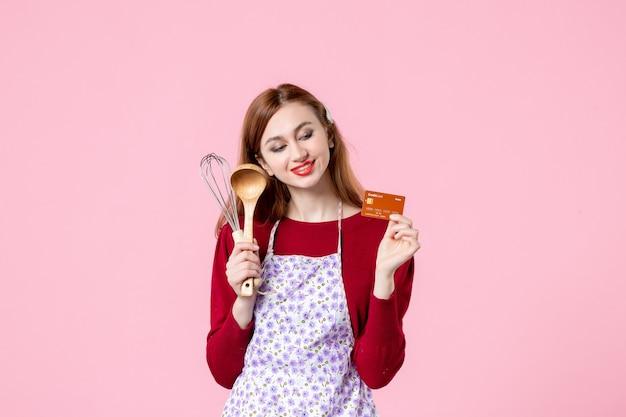 Widok z przodu młoda gospodyni trzymająca trzepaczkę i kartę bankową na różowym tle kuchnia ciasto ciasto kobieta zakupy kuchnia jedzenie kolor gotowanie