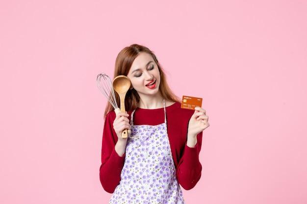 Widok z przodu młoda gospodyni trzymająca trzepaczkę i kartę bankową na różowym tle kuchnia ciasto ciasto kobieta zakupy pieniądze jedzenie kolor gotowanie