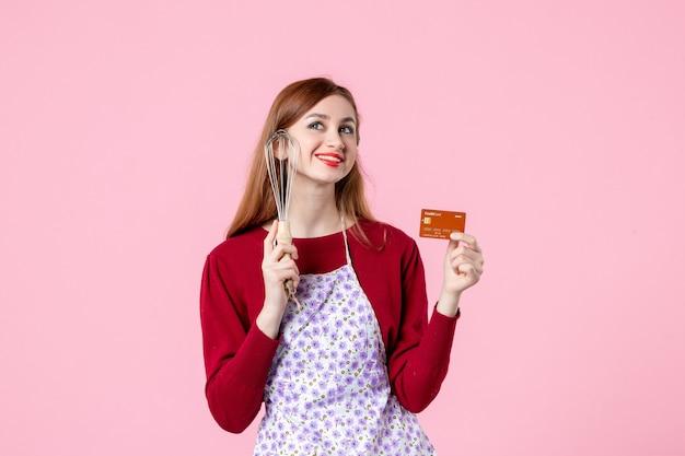 Widok z przodu młoda gospodyni trzymająca trzepaczkę i kartę bankową na różowym tle kuchnia ciasto ciasto kobieta zakupy pieniądze kuchnia jedzenie gotowanie