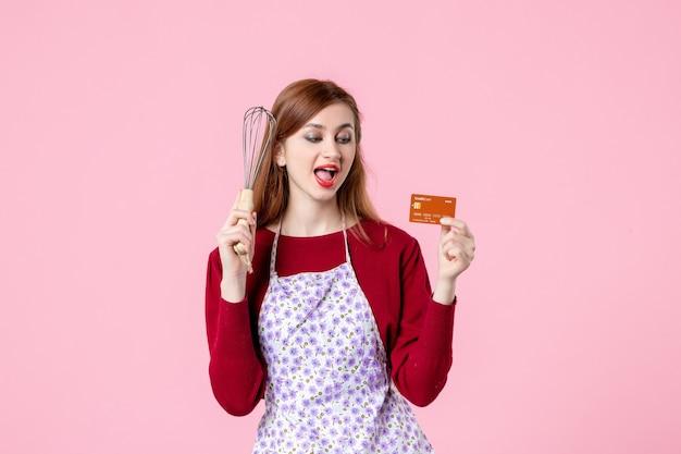 Widok z przodu młoda gospodyni trzymająca trzepaczkę i kartę bankową na różowym tle kuchnia ciasto ciasto kobieta zakupy pieniądze kuchnia jedzenie kolory gotowanie