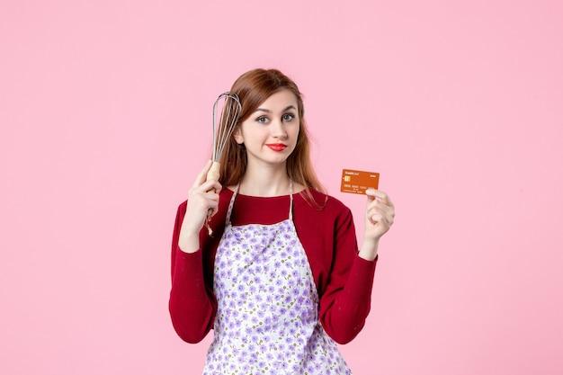 Widok z przodu młoda gospodyni trzymająca trzepaczkę i kartę bankową na różowym tle kuchnia ciasto ciasto kobieta zakupy pieniądze kuchnia kolor gotowanie