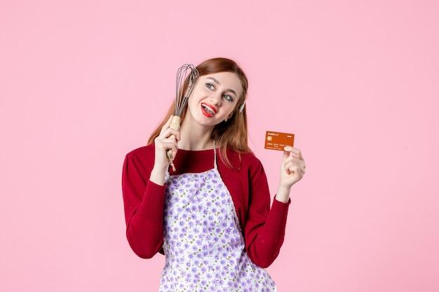 Widok z przodu młoda gospodyni trzymająca trzepaczkę i kartę bankową na różowym tle kuchnia ciasto kobieta zakupy pieniądze jedzenie piec gotowanie ciasta