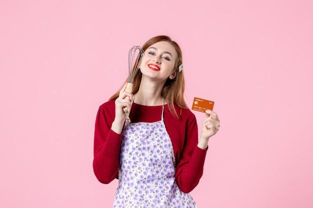 Widok z przodu młoda gospodyni trzymająca trzepaczkę i kartę bankową na różowym tle kuchnia ciasto kobieta zakupy pieniądze kuchnia jedzenie piec gotowanie ciasta