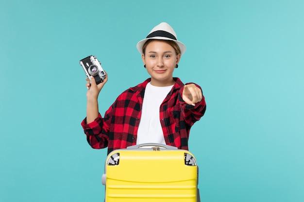Widok z przodu młoda kobieta będzie w podróży i trzymając aparat na niebieskiej przestrzeni