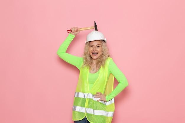 Widok z przodu młoda kobieta budowniczy w zielonym kasku kombinezonu budowlanego, po prostu pozuje z młotkiem i uśmiechem na różowej pani pracy budowlanej architektury kosmicznej