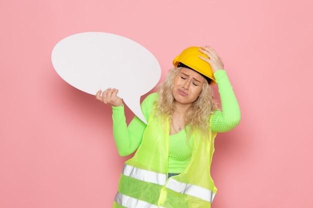 Widok z przodu młoda kobieta budowniczy w zielonym kasku kombinezonu budowlanego trzyma biały znak przygnębiony na różowej przestrzeni