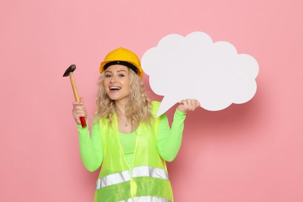 Widok z przodu młoda kobieta budowniczy w zielonym kasku kombinezonu budowlanego, trzymając biały znak z młotkiem na różowej przestrzeni