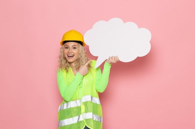 Widok z przodu młoda kobieta budowniczy w zielonym kasku kombinezonu budowlanego, trzymając biały znak ze szczęśliwym wyrazem na różowej przestrzeni