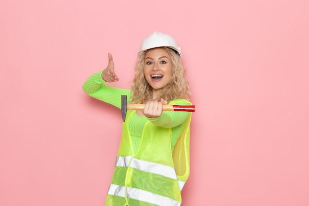 Widok z przodu młoda kobieta budowniczy w zielonym kasku kombinezonu budowlanego trzymając młotek z uśmiechem na różowej przestrzeni architektura pracy pani pracy budowlanej