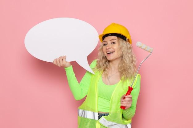 Widok z przodu młoda kobieta budowniczy w zielonym kasku kombinezonu budowlanego tylko pozuje z białym znakiem uśmiechając się na różowej architekturze kosmicznej pracy budowlanej pani