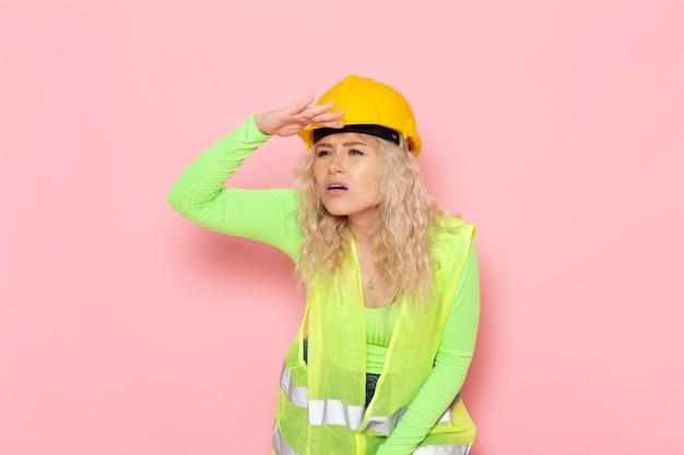 Widok z przodu młoda kobieta budowniczy w zielonym kombinezonie budowlanym żółty kask patrząc w dal na różowym miejscu pracy architektury pracy budowlanej