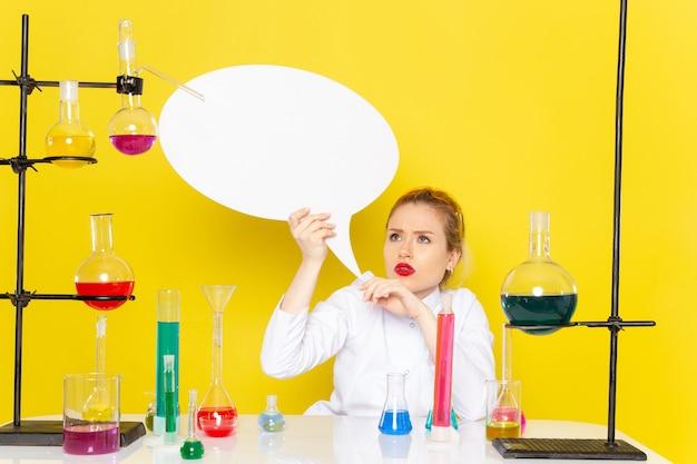 Widok z przodu młoda kobieta chemik siedzi w białym garniturze z różnymi roztworami, trzymając biały znak na żółtym procesie nauki chemii przestrzeni