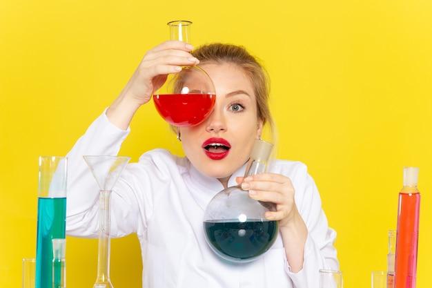 Widok z przodu młoda kobieta chemik w białym garniturze, posiadająca różne rozwiązania w żółtej przestrzeni chemii pracy