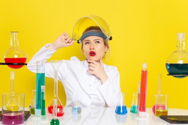 Widok z przodu młoda kobieta chemik w białym garniturze z roztworami ed myśli na temat żółtej kosmosu nauki chemii