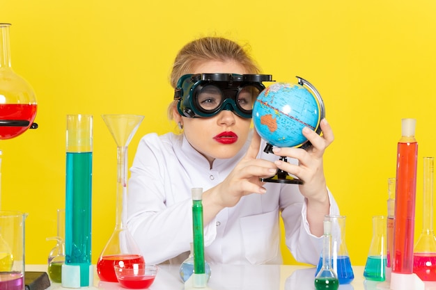 Widok z przodu młoda kobieta chemik w białym garniturze z roztworami ed sprawdzającymi globus z maską na żółtej przestrzeni nauki chemii