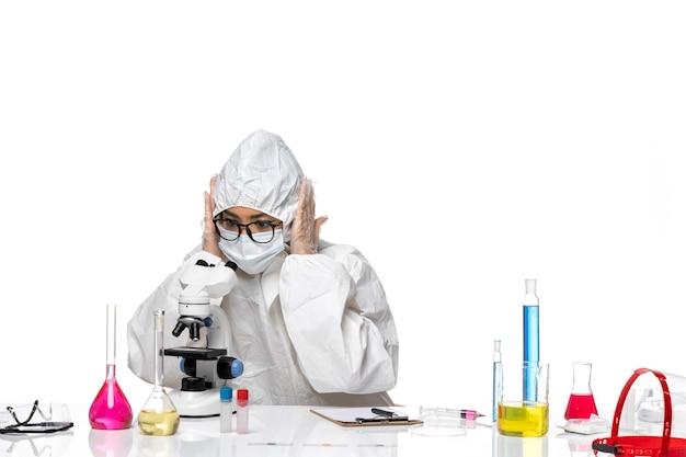 Widok z przodu młoda kobieta chemik w specjalnym kombinezonie ochronnym pracująca z mikroskopem na białym biurku wirus covid- laboratorium chemiczne