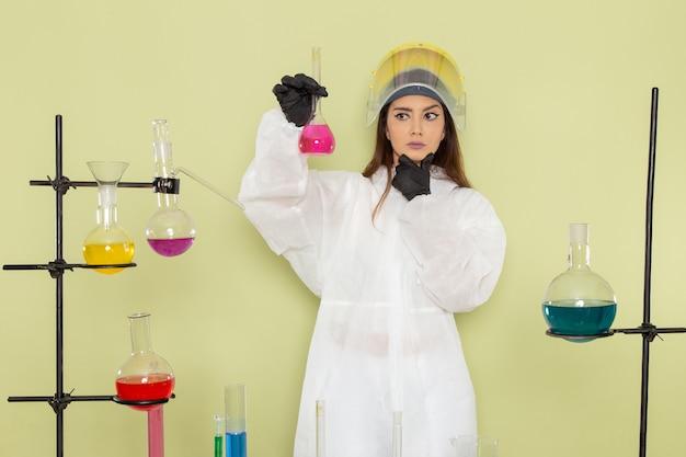 Widok z przodu młoda kobieta chemik w specjalnym kombinezonie ochronnym, pracująca z roztworami i myśląca na zielonej ścianie laboratorium chemii chemii praca kobieca nauka