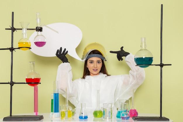 Widok z przodu młoda kobieta chemik w specjalnym kombinezonie ochronnym trzyma biały znak na zielonej ścianie praca laboratorium chemiczne chemia kobiet nauki