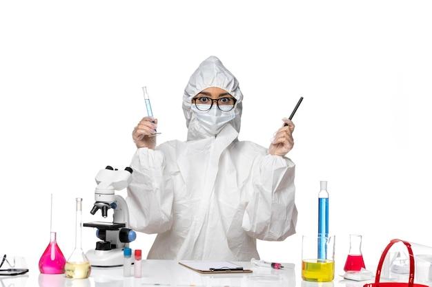 Widok z przodu młoda kobieta chemik w specjalnym kombinezonie ochronnym, trzymając maleńką kolbę na białym tle laboratorium wirus chemii covid