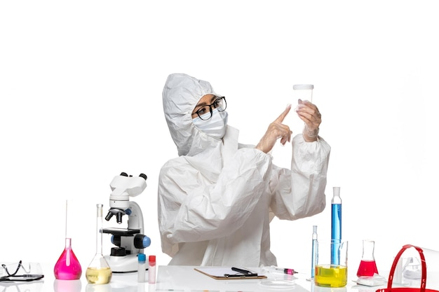 Widok z przodu młoda kobieta chemik w specjalnym kombinezonie ochronnym, trzymając pustą kolbę na jasnym białym tle laboratorium covid - zdrowie wirusa chemii