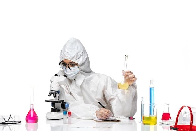 Widok z przodu młoda kobieta chemik w specjalnym kombinezonie ochronnym trzymająca kolbę z roztworem i za pomocą mikroskopu na białym tle laboratoryjny wirus chemii covid