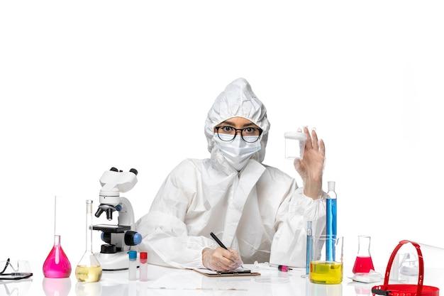 Widok z przodu młoda kobieta chemik w specjalnym kombinezonie ochronnym trzymająca pustą kolbę i pisząca na białym biurku laboratorium covid - zdrowie wirusa chemii