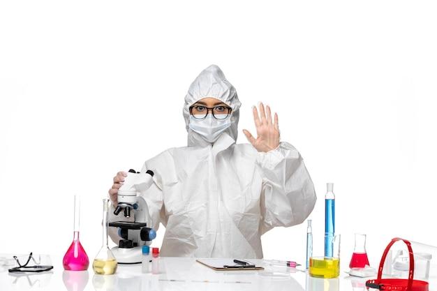 Widok z przodu młoda kobieta chemik w specjalnym kombinezonie ochronnym za pomocą mikroskopu i machając na białym tle laboratorium wirusów covid zdrowie chemia