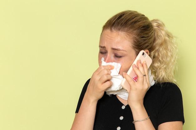Widok z przodu młoda kobieta czuje się bardzo chora i chora, rozmawia przez telefon na jasnozielonej chorobie lekarskiej ściany