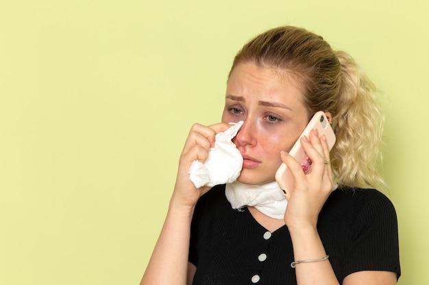 Widok z przodu młoda kobieta czuje się bardzo chora i chora rozmawia przez telefon na zielonej ścianie choroby lekarskiej
