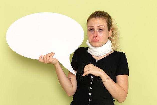 Widok z przodu młoda kobieta czuje się bardzo chora i chora, trzymając ogromny biały znak na zielonej ścianie choroba medycyna choroba
