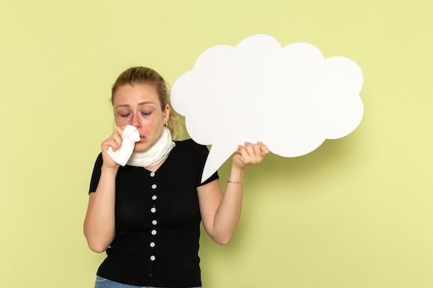 Widok z przodu młoda kobieta czuje się bardzo chora i chora, trzymając ogromny biały znak na zielonej ścianie