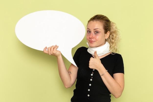 Widok z przodu młoda kobieta czuje się bardzo chora i chora, trzymając ogromny biały znak na zielonym biurku choroba medycyna choroba
