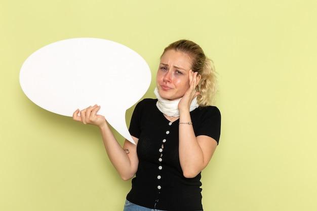 Widok z przodu młoda kobieta czuje się bardzo chora i chora, trzymając ogromny biały znak podkreślony na zielonej ścianie choroba medycyna choroba