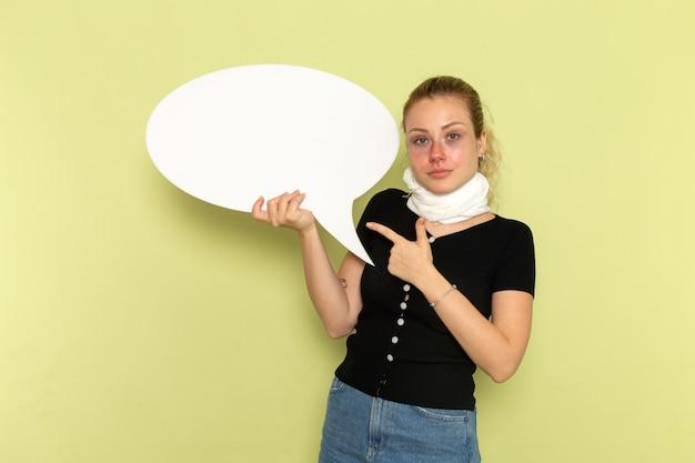 Widok z przodu młoda kobieta czuje się bardzo chora i chora, trzymając ogromny biały znak pozujący na jasnozielonej ścianie