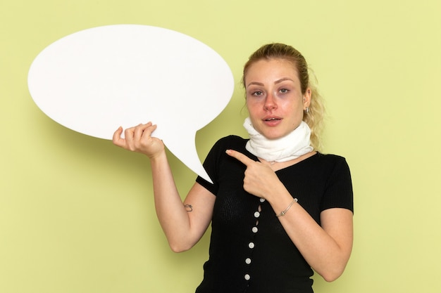 Widok z przodu młoda kobieta czuje się bardzo chora i chora, trzymając ogromny biały znak pozujący na zielonej ścianie choroba medycyna choroba