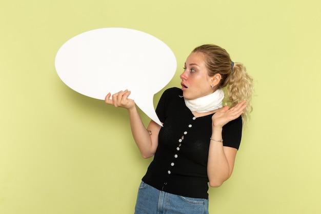 Widok z przodu młoda kobieta czuje się bardzo chora i chora, trzymając ogromny biały znak stwarzających na zielonym biurku mdłości medycyna choroba zdrowie