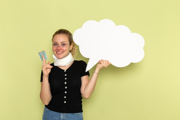 Widok z przodu młoda kobieta czuje się bardzo chora i chora, trzymając ogromny biały znak trzymając pigułki na zielonej ścianie choroba medycyna choroba
